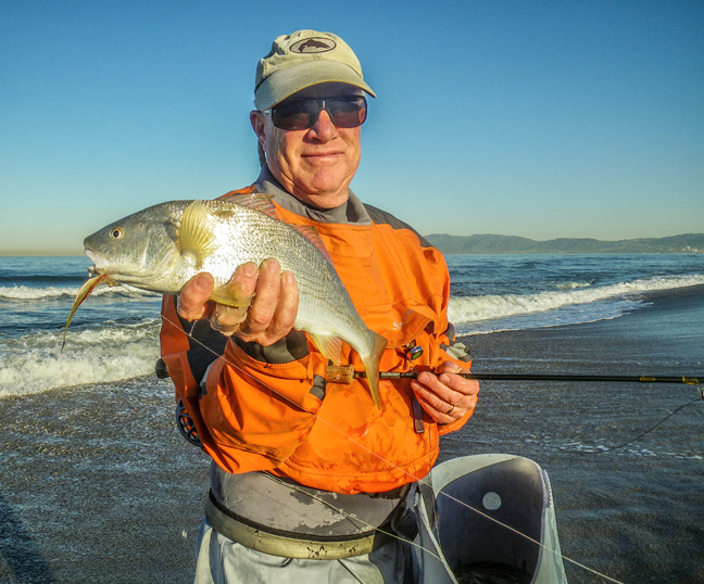 Surf buddy Jim Solomon with a fine yellowfin croaker that ate a small clouser in tight...photo by Al Q