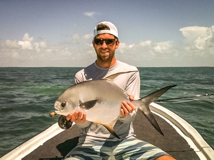 Angler Brett Bowen lands a beautiful permit off of Caye Caulker, Belize on a #6 tan merkin with orange legs and grizzly hackle claws. Photo courtesy of Brett Bowen.