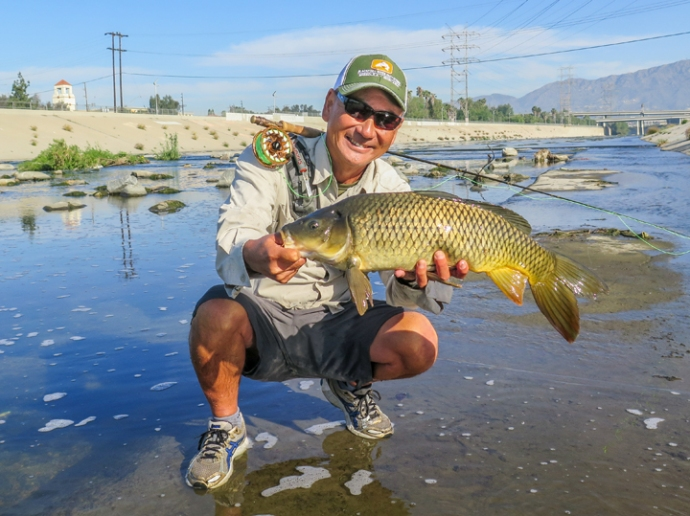Glenn Ueda is all smiles after masterfully landing this trophy LA river carp. His first carp on flyand it ate a #10,  red and black fly I tied. Photo by Al Q