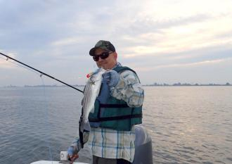 Little striper landed on a surface popper just at dusk. photo courtesy of Dan Blanton.